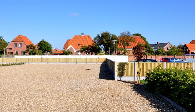 stakit ved en parkeringsplads i et dejligt sommervejr, med villaer i baggrunden