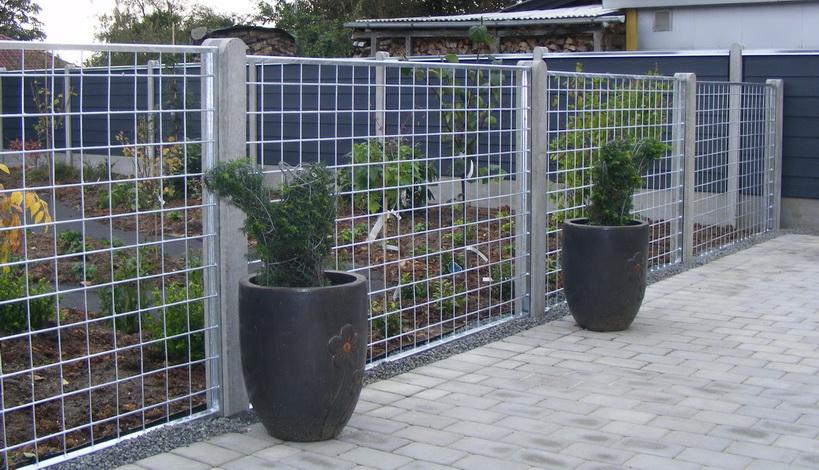 Her ses et hegn lavet at jern, der er galvaniseret. Stolperne er lavet af beton.